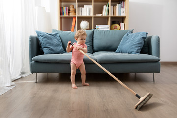 baby sweeping living room floor with broom