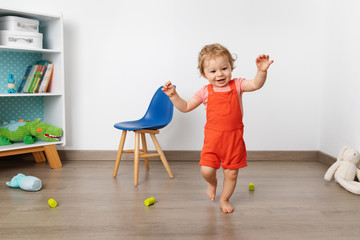 Baby making first steps in playroom