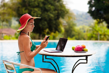Woman with laptop at swimming pool. Remote work.