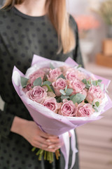 Beautiful bouquet of pastel purple roses in womans hands. the work of the florist at a flower shop. Delivery fresh cut flower. European floral shop.