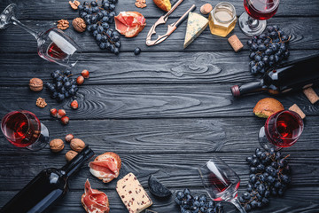 Frame made of delicious wine with snacks on dark wooden background