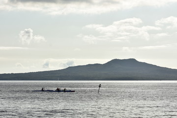 Crews paddling hard on board waka ama in calm channel in front of island with volcanic cone.