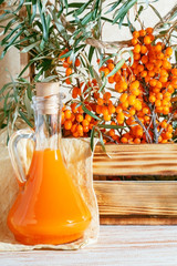 Vegetarian food, healthy nutrition, preserving the harvest of ripe juicy sea buckthorn, preparing fresh healthy vitamin drink and healing broth. Jug with juice and branches of sea buckthorn