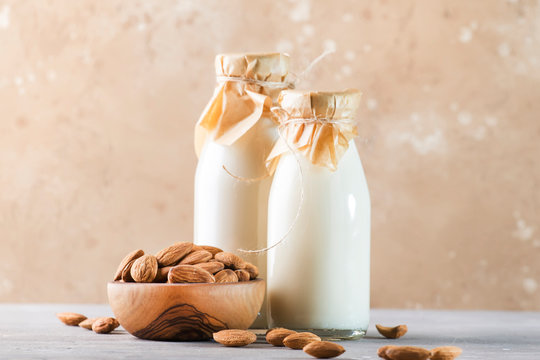 Vegan almond milk and cream in bottles, closeup, brown background. Non dairy alternative milk. Healthy vegetarian food and drink concept. Copy space