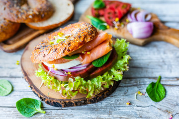 Bagel with salmon and fresh vegetables.