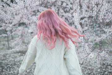 Pink haired woman spinning in front of almond blossom tree