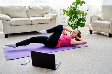 Beautiful young woman training online at home on laptop computer, copy space. Full length portrait. Yoga, pilates, working out exercising Wall mural