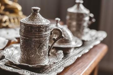 Obraz Closeup shot of an antique silver tea set with a blurry background - fototapety do salonu