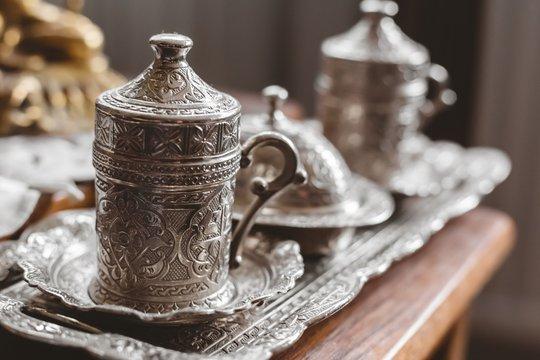 Closeup shot of an antique silver tea set with a blurry background