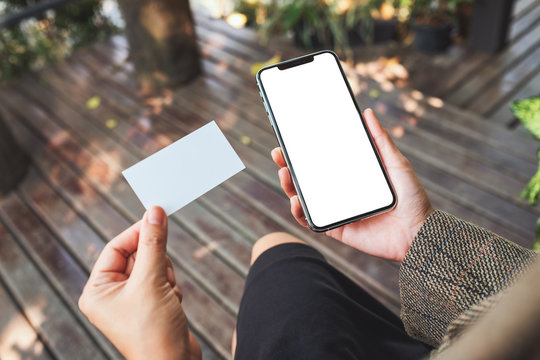 Mockup image of a woman holding white mobile phone with blank desktop screen and a white empty business card