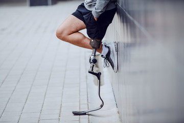 Fotomurales - Cropped picture of sportsman with artificial leg standing against the wall and holding hands in pockets.