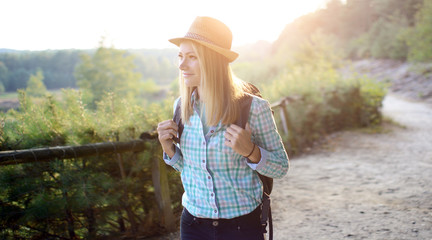 Woman with backpack hiking through forest and nature on a sunny summer day