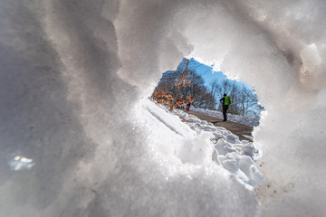hiker seen from an ice grotto