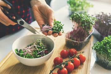 woman prepare fresh raw vegan salad from microgreens and vegetables