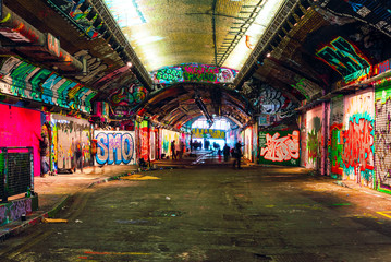 Poster Graffiti London, UK/Europe; 21/12/2019: Leake Street, underground tunnel with graffiti covered walls in London. Scene with pedestrians and graffiti artists.