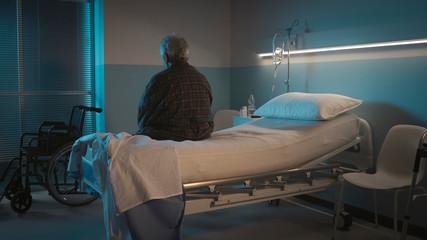 Obraz Depressed senior sitting on the hospital bed alone - fototapety do salonu