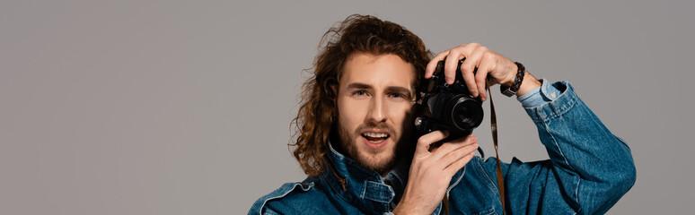 panoramic shot of smiling man in denim jacket holding digital camera isolated on grey