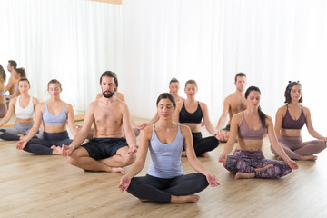Fotomurales - Group of young sporty attractive people in yoga studio, practicing yoga lesson with instructor, sitting on floor in Siddhasana, easy seated yoga pose. Healthy active lifestyle, working out in gym.