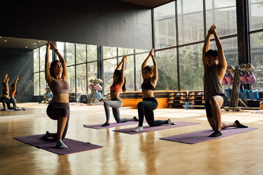 Group of Asian women and man doing pilates lying on yoga mats in aerobics class. Young sporty people on bended knee on the floor and put hands up in gym studio.