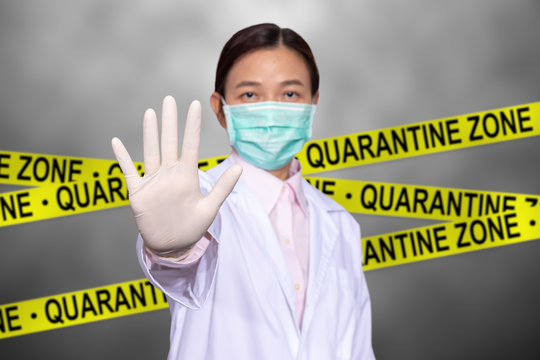 Asian female doctor wear a medical mask, raise hand for stop sign to do not enter quarantine area with yellow quarantine sign on the back, entrance is forbidden in quarantine zone.