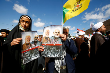 "Iranian people carry pictures of the late Iran's Quds Force top commander Qassem Soleimani and Iraqi militia commander Abu Mahdi al-Muhandis during the forty days memorial, at the ""Valley of Peace"" cemetery in Najaf"