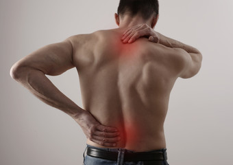 Muscular Man suffering from back and neck pain. Chiropractic concept. Sport exercising injury