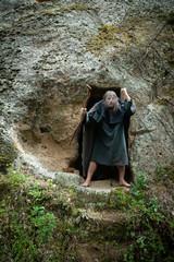 Fluchender Einsiedler vor seiner Wohnhöhle