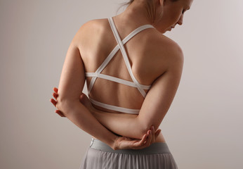 Woman suffering from back and pain. Scoliosis posture correction, muscles straching,ballet body exercises