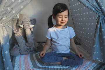 The child does yoga. Little girl is sitting in lotus position. Children's yoga for spinal health.