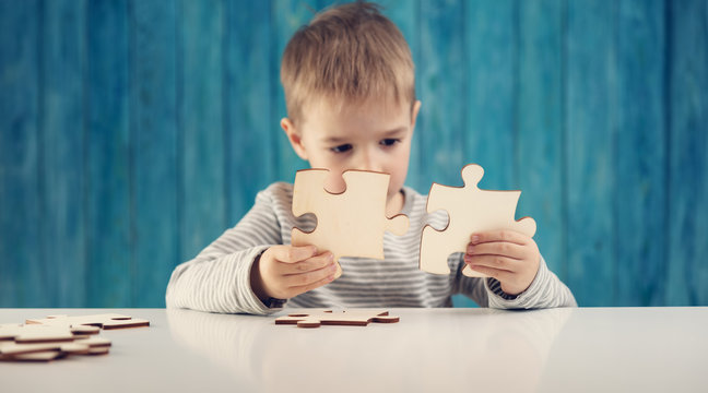 Little child holding puzzle pieces and trying to solve it