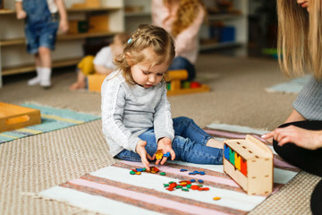 Caucasian toddler girl playing Montessori center