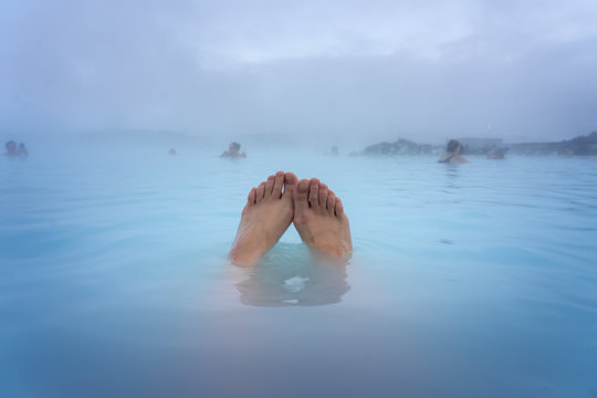 Feet of a woman bathing in the Blue Lagoon next to Reykjavik with people bathing in this natural hot spring