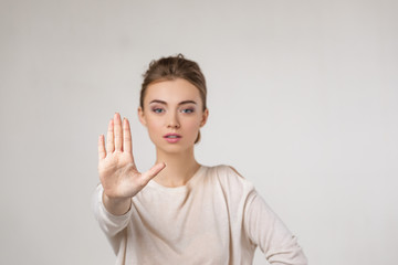 beautiful young woman making stop gesture on gray background. Wall mural