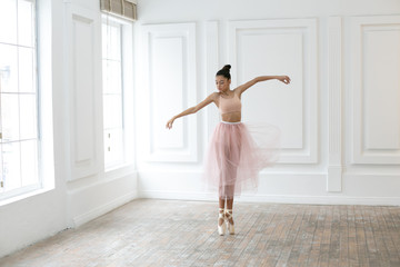 horizontal photo of a dancing ballerina in a bright class