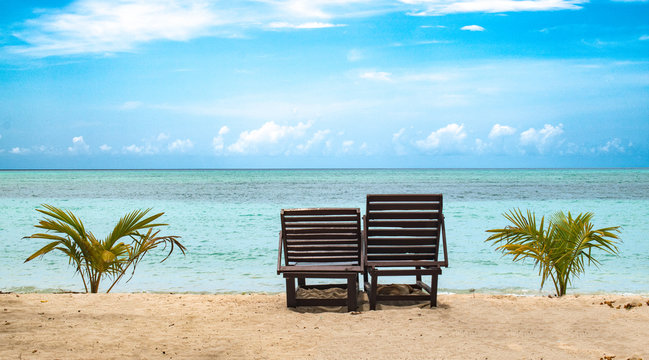 Beautiful photo of two wooden recliner chairs lying vacant for tourists and honeymoon couples on beach for good times, amidst clear blue sky, calm ocean of turquoise color water and visible horizon.