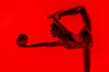 Young flexible girl isolated on red studio background. Teen-age female model as a rhythmic...