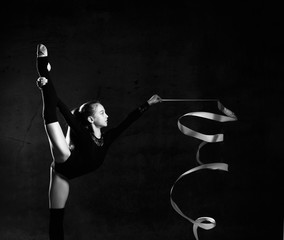 Young girl gymnast in black sport body and uppers standing with streched leg and making exercise with gymnastic tape