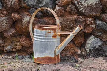 old rusted metallic watering can, with rocky wall background
