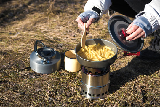 close up of hiker's hands cooking pasta on portable wood stove. Cooking pasta in mountains