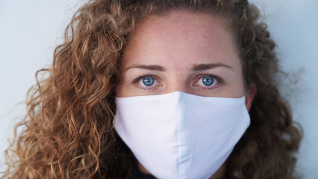 beautiful blond-haired curly girl in a medical mask on a light background. Serious blue-eyed girl in a respirator. safety from diseases. respiratory disease prevention. cruise ship