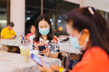 Female passenger at the airport wearing protective mask and using cell phone.