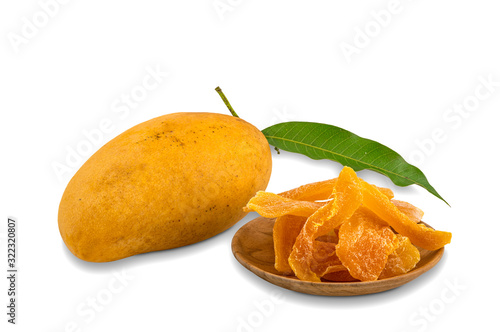 Fototapete Pile of dehydrated mango in wooden plate and ripe mango with green leaf