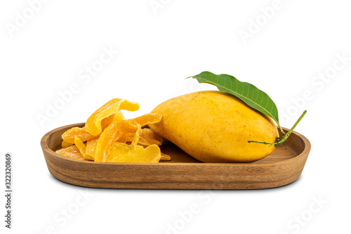 Fototapete Pile of dehydrated mango and ripe mango with leaf in a wooden tray on white background with clipping path.