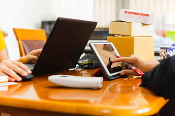 Businesspeople working on tablet from home on desk with postal parcel on table.