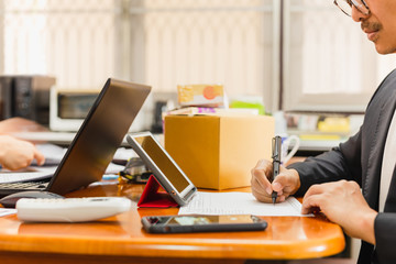 Businessman hand writing on paperwork with tablet and parcel box on table.