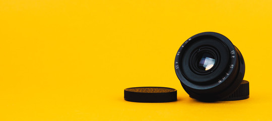 Photo lens on yellow background. Copy space for text or design