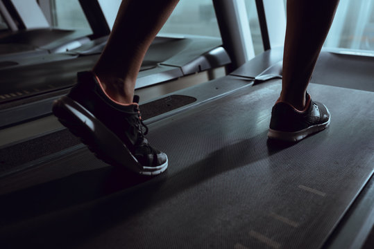 Cropped view of african american woman legs wearing sneakers on treadmill in gym