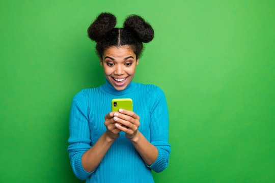 Photo of funky beautiful dark skin lady hold telephone hands open mouth check comments followers post repost wear blue turtleneck jumper isolated green color background
