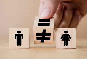 Hand flipping wooden equal and unequal cubics between man and woman.Gender equality concept.