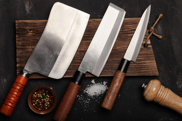 Chopping knives and spices on a dark table Wall mural